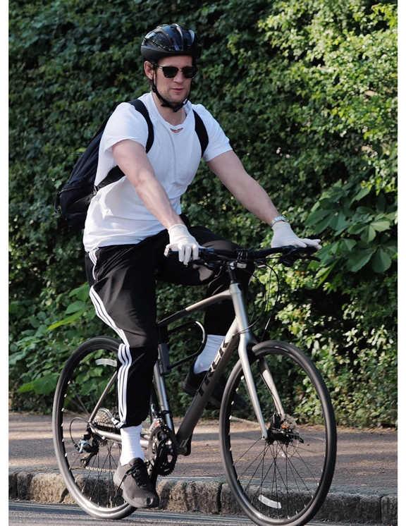 """サイクリング中のマットは、コリンと同じく〈アディダス オリジナルス〉のライン入りパンツ。裾を白ソックスに入れてチャリ仕様に。面白いのは、トップから白黒白黒とサンドイッチでコーデされているところ。白と黒が丁度半分ずつで、バランスよくまとまっている。で、そのコーデに馴染んでいるグレーのバイクは〈トレック〉。恐らくこちらは高性能フィットネスバイクの""""FX Sport4""""と見受けられる。これもまた、コーデのひとつのようでお洒落。"""